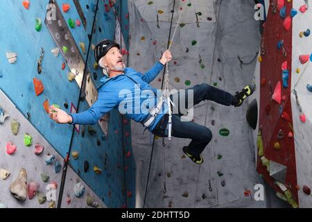 Professional senior man flying after jump while he is climbing on an artificial rock climbing wall. Extreme sports concept.