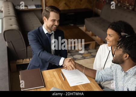 Happy biracial couple handshake male realtor at meeting