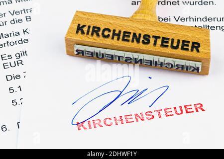 Ein Stempel aus Holz liegt auf einem Dokument. Aufschrift Kirchensteuer