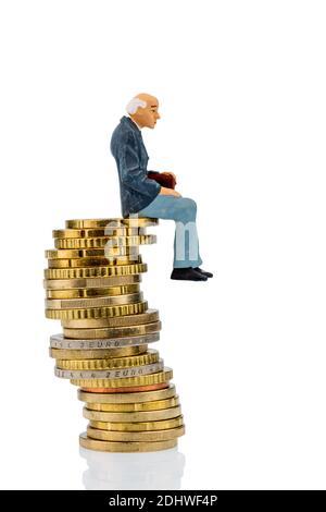 Rentner sitzt auf einem Stapel Euromünzen, Symbolfoto für Pension, Altersvorsorge, Alterssicherung - Stock Photo
