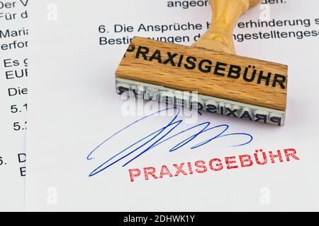 Ein Stempel aus Holz liegt auf einem Dokument. Aufschrift Praxisgebühr