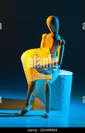 Eine Figur mit Toiletten Papier. Symbolphoto für Darmerkrankung Stock Photo