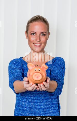 Eine junge Frau hält ein Sparschwein in ihrer Hand. Symbolfoto für Sparen, Geld anlegen und Altersvorsorge. - Stock Photo