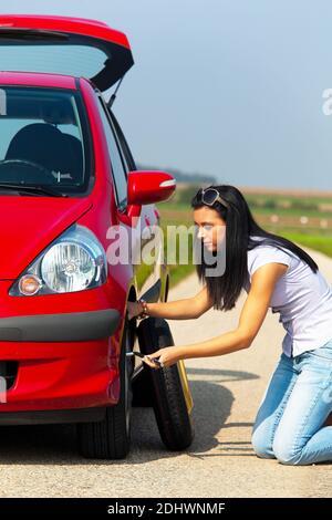 Junge Frau mit einer Reifenpanne am Auto - Stock Photo