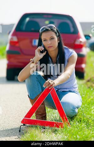 Junge Frau mit einer Reifenpanne am Auto, Warnkreuz wird aufgestellz, - Stock Photo