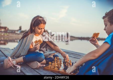 Two  little friends, boy and girl having fun while playing chess sitting by the lake in the evening. Kids are playing. Friendship. Selective focus.
