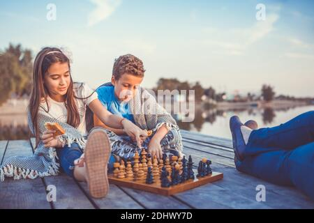 Two young cute little friends, boy and girl having fun while playing chess sitting by the lake in the evening. Kids are playing. Friendship. Selective