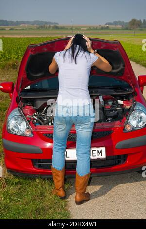 Junge Frau hat eine Autopanne, Motorschaden,  MR: Yes Stock Photo