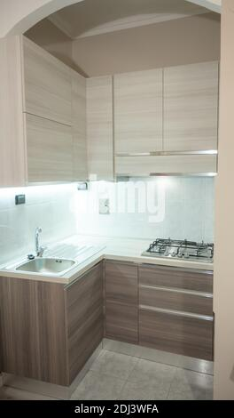 View of a modular corner kitchen in gray and brown color, the led under-cabinet light attracts attention.