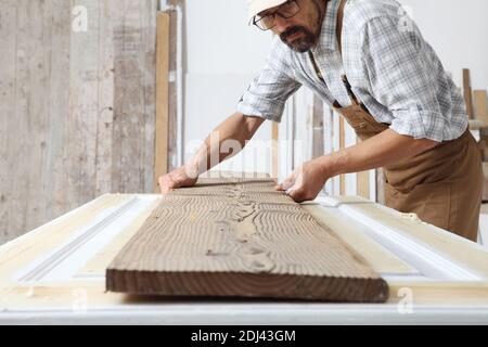 Male carpenter working the wood in carpentry workshop, holding wooden plank, wearing overall