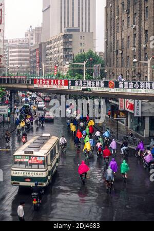 Cyclists in multi coloured macs on a rainy day on Nanjing Road (Nanjing Lu) Shanghai, China, June 1995 - Stock Photo