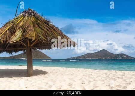 Caribbean View from Mopian Island: Parasol, Sandy Beach, Islands of Petit Martinique and Petit Saint Vincent: Saint Vincent and the Grenadines.