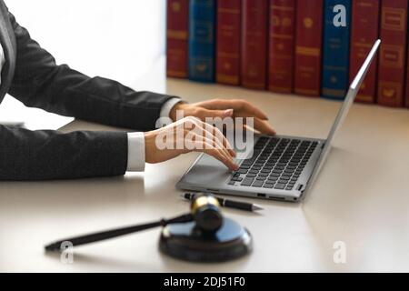 Female hands with a judge's gavel in front of a laptop monitor. Lawyer's office.