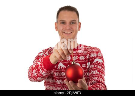 Young cheerful man wearing winter style knitwear is holding a red Christmas globe on isolated background