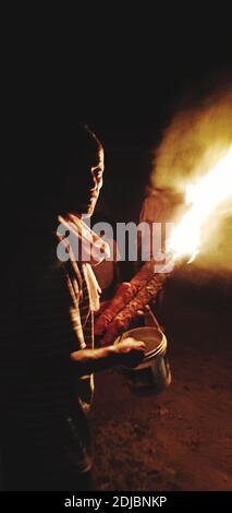 Side View Of Mature Man Holding Fire While Standing Against Sky At Night