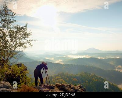 Nature photographer stay at tripod on summit and thinking. Hilly foggy landscape in first autumnal colors. Stock Photo