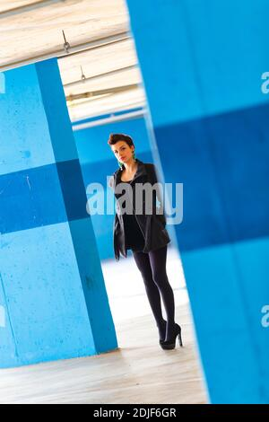 Teengirl in empty parking lot with Blue walls legs heels eyeshot eyes eye contact looking at camera tight space serious unsmiling - Stock Photo