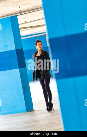 Teengirl in empty parking lot with Blue walls legs heels tight space serious unsmiling looking away aside back Stock Photo