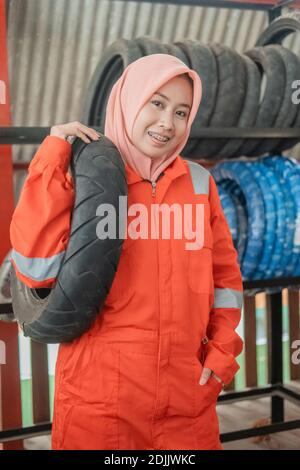 veiled female mechanic wears a wearpack uniform when carrying a motorbike tire while in a motorcycle repair shop