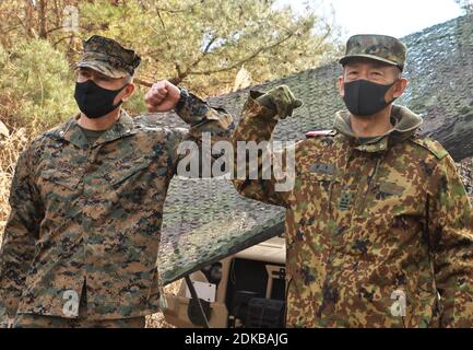 Shinto, Japan. 15th Dec, 2020. U.S. Marine Corps Lt Col Neil Berry and Japan Ground Self-Defense Force, Col Yuichiro Endo (R) bump elbows as United States Marines and Japan Ground Self-Defense Force personnel take part in the joint military exercise 'Forest Light 21' at Camp Soumagahara in Gunma prefecture, Japan on Tuesday, December 15, 2020. The annual military exercise this year is focused on seizing and defending key maritime terrain and islands supporting naval operations in the defense of Japan. Photo by Keizo Mori/UPI Credit: UPI/Alamy Live News