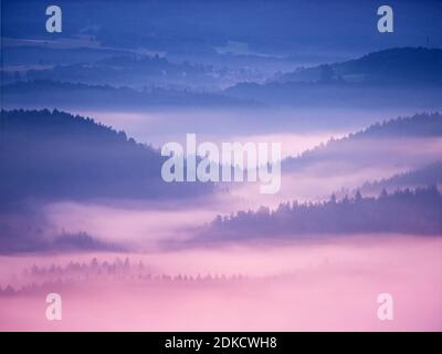 Pink daybreak in hilly landscape. Autumn misty morning in a beautiful rocky  hills. Peaks of hills are sticking out from fog. Miracle of nature Stock Photo