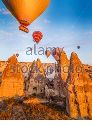 Bright yellow sunrise with colourful balloons floating just above cave homes in Cappodocia