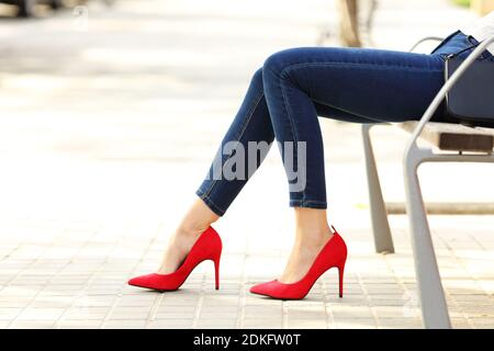 Side view portrait of a beauty woman legs with jeans and high heels sitting in a bench - Stock Photo