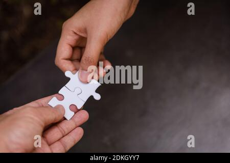 Close up couple hands of man and woman connecting jigsaw puzzle together.