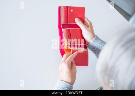 close up of hands of mature woman looking and revising how many money she have in her wallet - empty wallet and needing money concept and lifestyle - Stock Photo