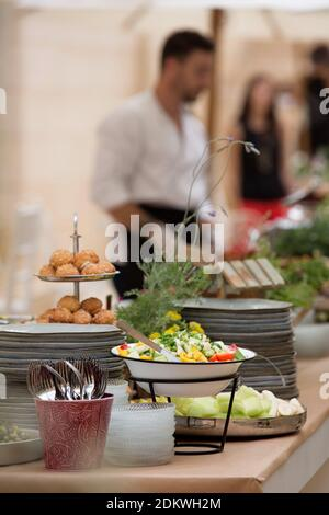 An assortment of foods in bowls on a buffet table during a evening event - Stock Photo