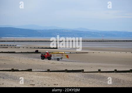 The RNLI Beach Patrol on duty on an empty Rhyl beach, Wales - Stock Photo