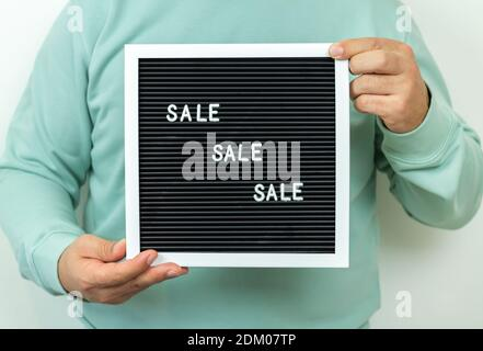 Man holding signboard with text SALE. Black Friday or Cyber Monday concept