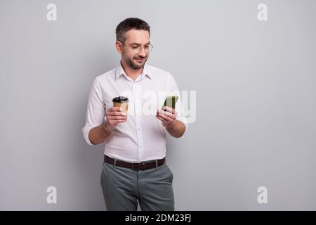 Portrait of his he nice attractive cheery elegant classy mature man holding in hands cell chatting online drinking cacao isolated over light gray