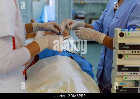 Doctors and nurses are using tools to anesthesiologist procedures on patient in the anesthetic machine inside operating room. - Stock Photo