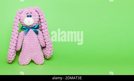 Toy pink bunny or hare with a bow on a green background, space for text - Stock Photo