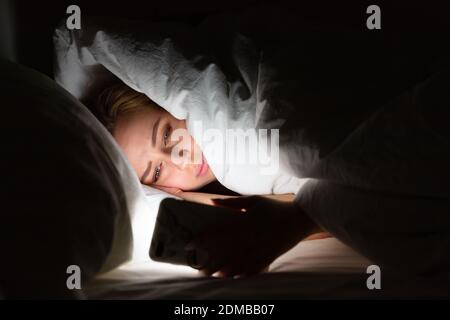Woman lying in bed under the blanket using smartphone late at night, can not sleep, addict news about Covid-19 or scrolling social networks. Insomnia, nomophobia, sleep disorder.