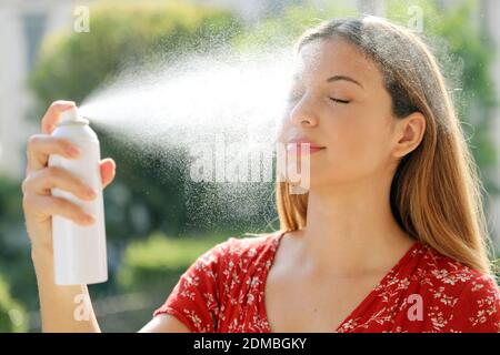 Young woman applying thermal water on face outdoor. Thermal water used for skin care, fix makeup, help skin irritation, redness and insect bites.