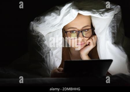Woman lying in bed under the blanket using tablet late at night, can not sleep, news search about Covid-19 or scrolling social networks. Insomnia, nomophobia, sleep disorder.