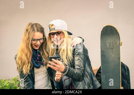 Best friends enjoying time together outdoors with smartphone - Concept of new trends and technology with hipster girlfriends having fun in urban city area - Alternative four seasons fashion clothes
