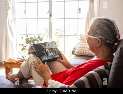 Senior woman red dressed lying in sofa at home using tablet device to video call with a couple of friends absent due to coronavirus - on the screen two elderly people with hat doing ok with hand