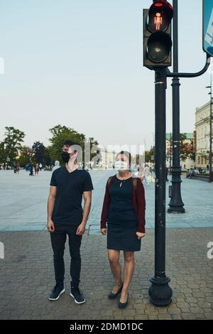 Man and woman waiting at pedestrian crossing next to traffic lights in the city center looking away wearing the face masks to avoid virus infection and to prevent the spread of disease in time of coronavirus - Stock Photo