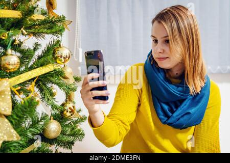 Woman female sitting at home in front of the christmas tree taking photos selfies using smart mobile phone video chat family