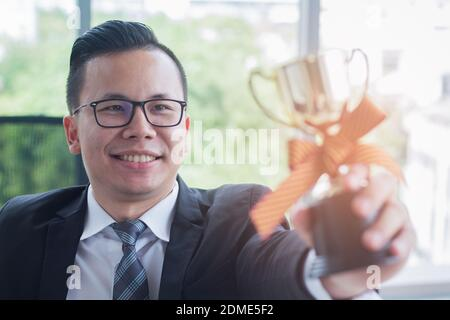 Young business man holds an excellent businessman trophy with joy and happiness The concept of a successful new generation