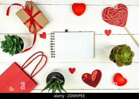 Creative Valentine Day romantic composition with red hearts, satin ribbon, lollipop, gift box and paper bag on white background. Mockup with copy spac