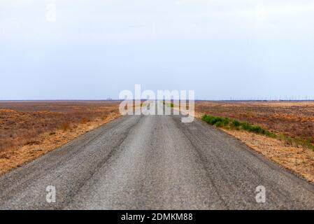 Long road stretching out into the distance in steppe. Stock Photo