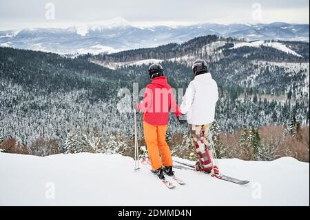Back view of couple skiers wearing ski suits and ski equipment in winter mountains, enjoying snowy weather, skiing and incredible landscapes. Concept of winter sport activities, relationships. - Stock Photo