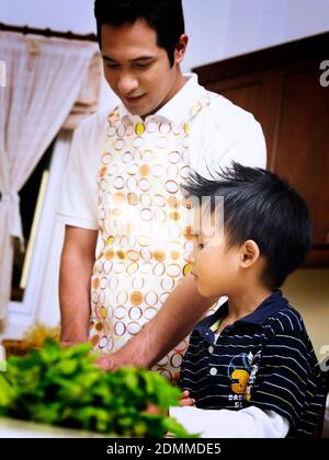 Son observing father in the kitchen - Stock Photo