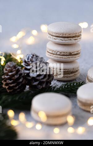 Vanilla macarons stacked on a white table, winterly decorated with fir branches and pine cones, a sring of light shines in the background
