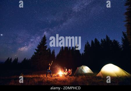 Man showing his friends Milky Way over tent city. Guys are sitting by the campfire on the background of the spruce forest and enjoying the evening starry sky. Outdoor recreation, touristm concept