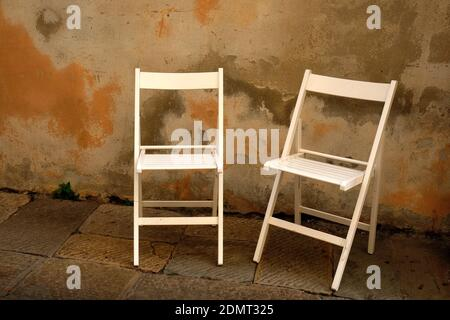 Empty Chairs On Footpath Against Wall